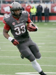In this Nov. 23, 2013, file photo, Arkansas' Korliss Marshall (33) carries in the first half of a game in Little Rock. Marshall will return to the Razorbacks in 2014.