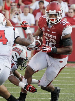 In this Aug. 31, 2013, file photo,<137> Arkansas running back Jonathan Williams (32) carries past Louisiana-Lafayette defenders a game in Fayetteville. Williams is returning to the Razorbacks in the 2014 season.