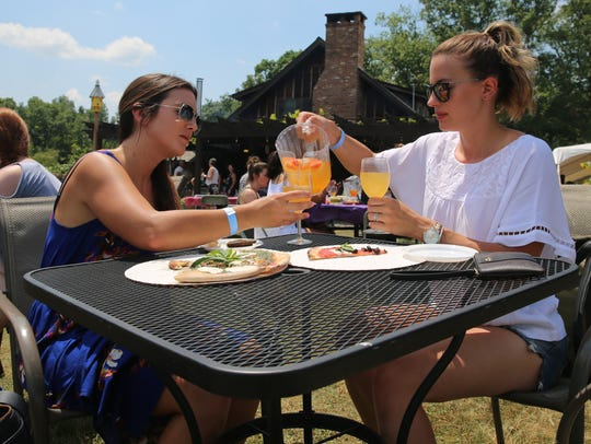 Jillian Paige-Lyons (right) pours sangria for her friend,