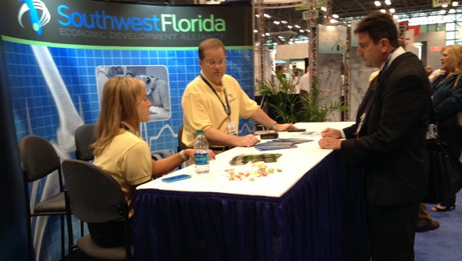 Southwest Florida Economic Development Alliance members Kristi Bartlett and John Cox talk with Ronald Harland, a pharmaceutical businessman from Yardley, Penn., at a medical device trade show in New York City.