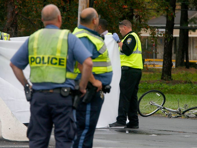 A sheet surrounds the body of a bicyclist who was struck