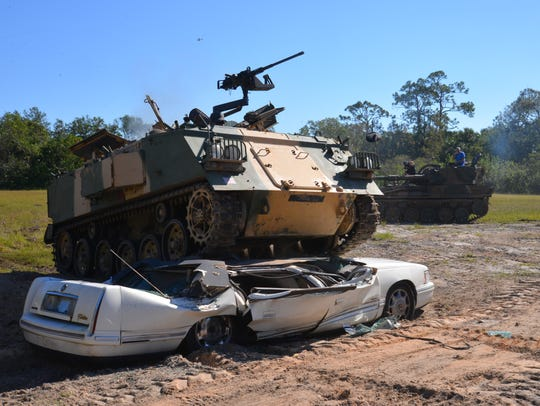 An Abbot FV432 armored personnel carrier crushes a Cadillac DeVille Friday at Tank America in Melbourne.