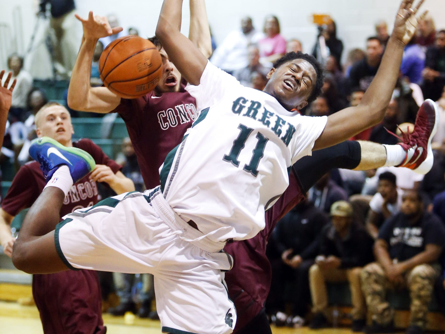 Concord's Robert White (left) fouls Mount Pleasant's Richard Caldwell on Dec. 15. The top-ranked Green Knights will be one of six Delaware teams playing in the upcoming Slam Dunk to the Beach boys basketball showcase at Cape Henlopen High.