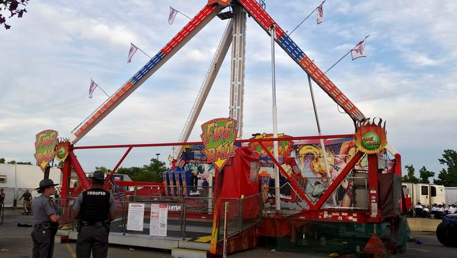 Authorities stand near the Fire Ball amusement ride after it malfunctioned, injuring several at the Ohio State Fair, Wednesday, July 26, 2017, in Columbus, Ohio. Some of the victims were thrown from the ride when it malfunctioned Wednesday night, said Columbus Battalion Chief Steve Martin.