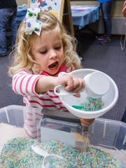 Audrey Muscatello of Pewaukee tries an experiment during the Wisconsin Science Festival event at the Pewaukee Public Library in 2015. This year the library will host a number of activities throughout the day Saturday, Nov. 4 as part of the statewide fair.