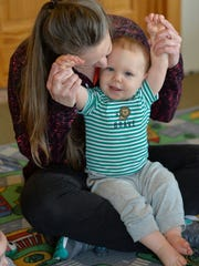 Kelly Martini plays with Abel Sand, 11 mos., at Martini's in-home child care near Avon. There has been a decline statewide in the number of in-home child care facilities and a shortage, especially in infant care.
