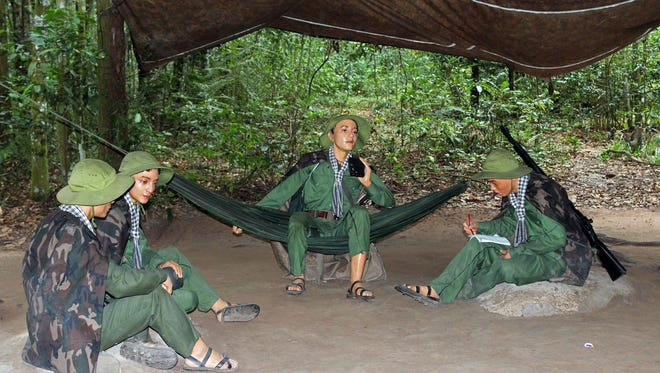 Dioramas at Cu Chi Tunnels show average people during wartime in the forested area.