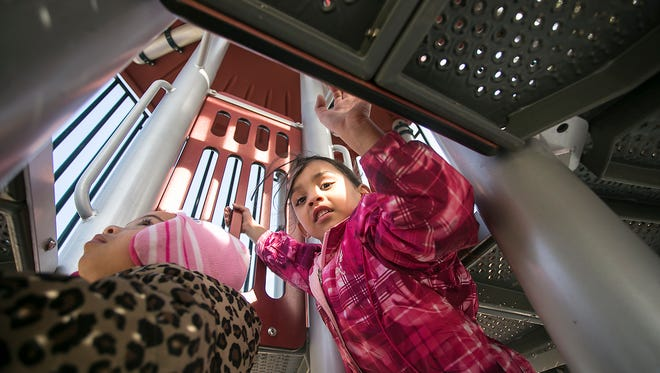 Samyrah Watford, 3, left, and Dayania Cagel, 5, both of York City, climb up the stairs on the playscape Saturday Feb. 20, 2016 at Penn Park. Amanda J. Cain photo