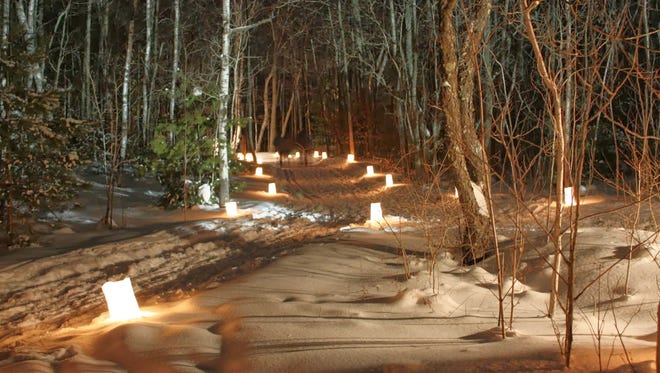 Candle luminaries light a path in Peninsula State Park for a candlelight ski and snowshoe event.