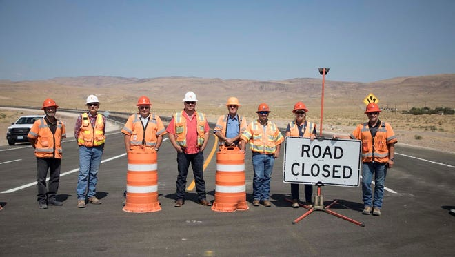 Crews stand on the USA Parkway just before it opened to traffic.