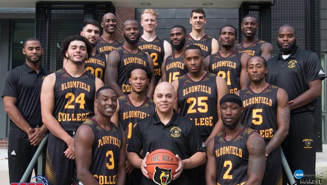 Bloomfield College men's basketball coach Gerald Holmes (holding ball) and 2017-2018 team.
