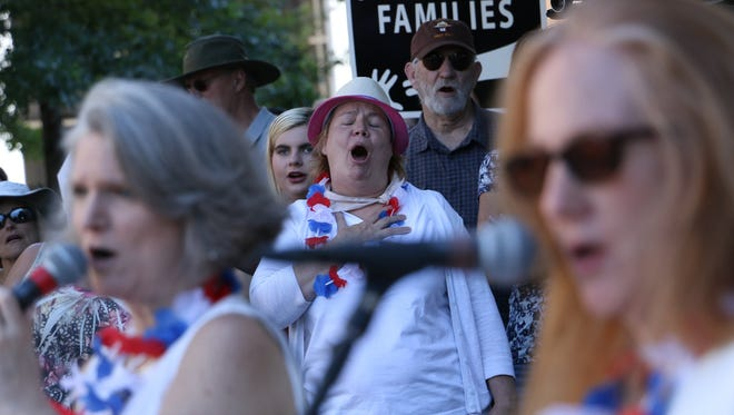People take part in the Families Belong Together rally and march in downtown Reno on June 30, 2018.