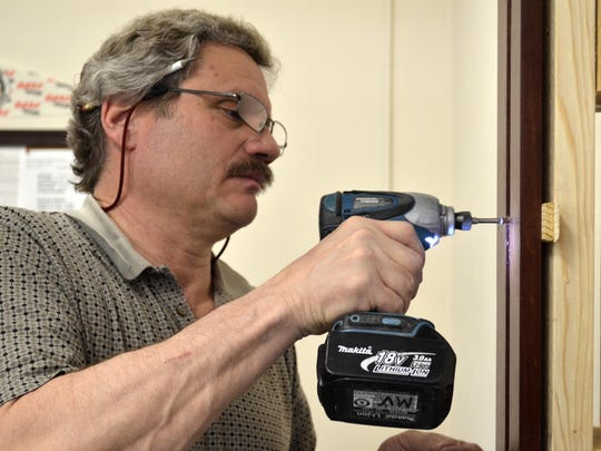 Mark Voeller of Lee Sowers Construction drills the new door frame together inside the Cascade County Clerk of Court's office.