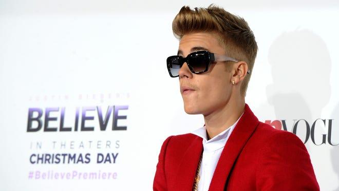 "Singer/producer Justin Bieber arrives at the premiere Of Open Road Films' ""Justin Bieber's Believe""  at Regal Cinemas L.A. Live on December 18, 2013 in Los Angeles, California."