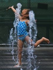 Graceland Kron, 4, gets some cooling relief from a