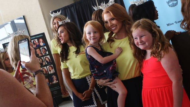 Miss University of Louisiana at Monroe Ashlynn Lanford poses with Quinn Wyatt and Rowan Wyatt, 8, as their mother Megan takes their photo after a press conference during which Miss Louisiana 2017 contestants introduced themselves in the lobby of the Howard Theatre at the Monroe Civic Center in Monroe, Monday, June 19, 2017. Rowan Wyatt is one of Lanford's Fleur de Lis Princesses who will escort her onstage during the pageant.