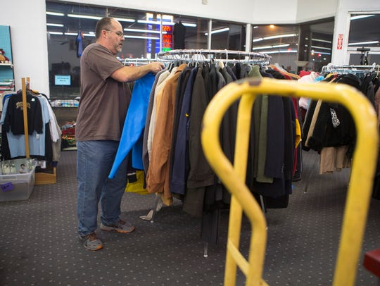 Hippo Thrift owner Alan Rash organizes coats at his