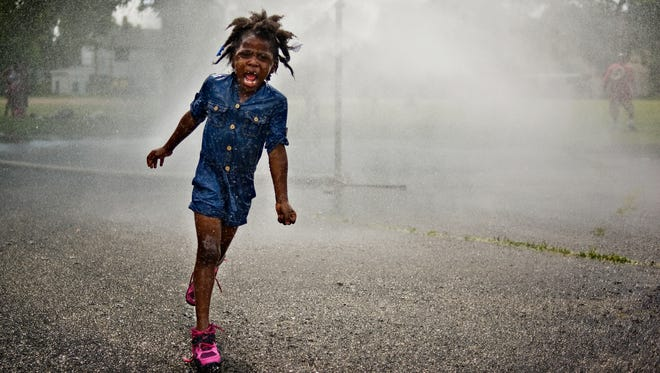 Mark Felix, whose work will be at Thomas Duncan Hall, worked at the Milwaukee Journal Sentinel. Here a girl runs through a sprinkler on a hot day in Wisconsin.