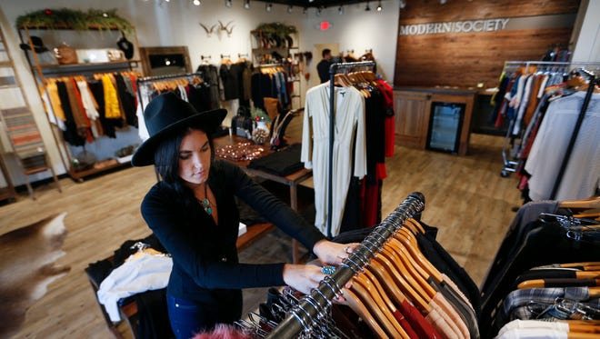 Modern Society co-owner Andrea Pena hangs clothes on racks at her store on Thursday, Dec. 9 2016.