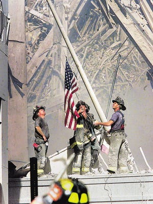 Part of a sequence of photos of three NYC firemen raising a flag at Ground Zero taken on 9/11 of the terrorist attacks that brought down the World Trade Center Twin Towers.