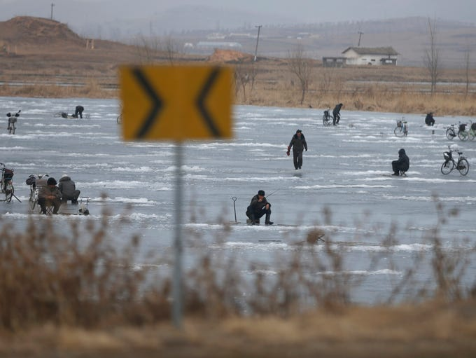 North Korean men ice fish on a frozen lake in Nampo,