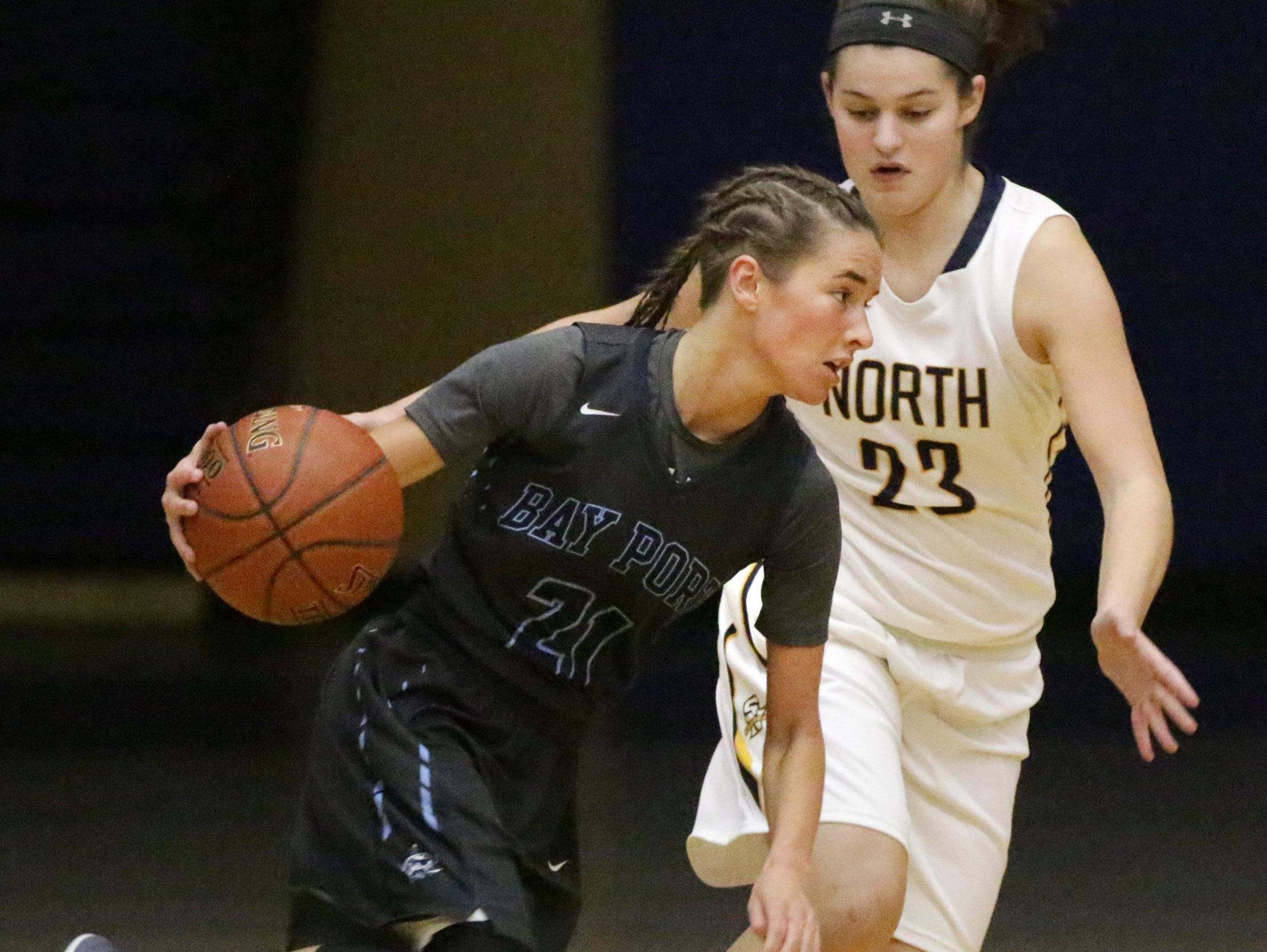 Bay Port's Meg Knutson (21) drives the ball by Sheboygan North's Meridith Opie (23) in a FRCC girls basketball game Friday at North.