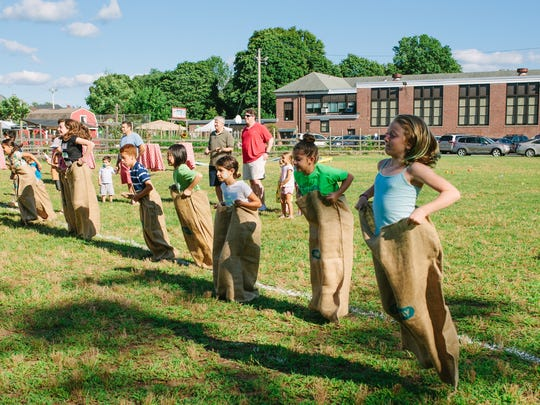 Off to the potato sack races! Kids hopping for a chance to win the coveted race trophy.