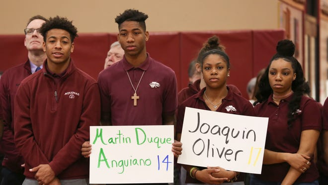 Students at Aquinas Institute lined the field house in a circle on Wednesday morning, March 14 and held signs of the names of the lives that were lost during the tragedy in Parkland, Florida.