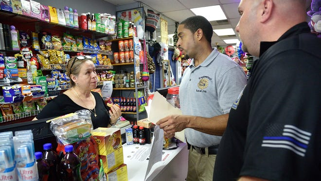 Englewood police Detective Miguel Sanchez, center, and Detective Dennis Conway of the Bergen County Prosecutor's Office speak with Aura Zapata as they cover Palisade Avenue in Englewood handing out fliers about the man who attacked an 83-year-old woman on July 28.