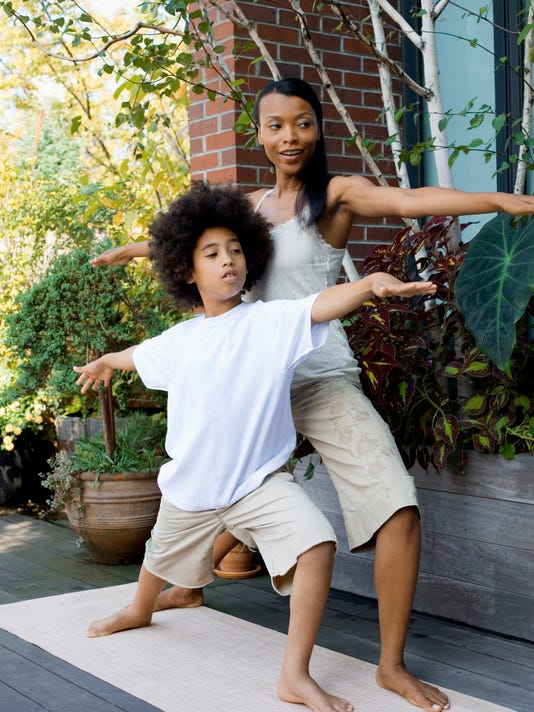Mother and son exercising together outdoors