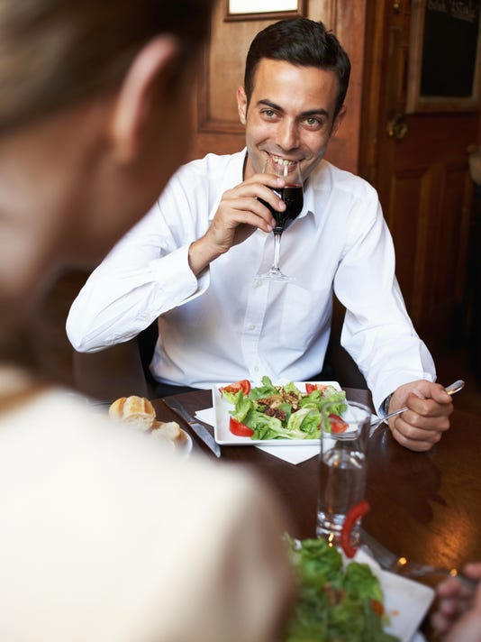 Young couple at restaurant table, man drinking red wine, smiling