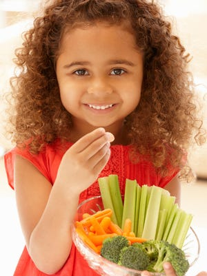 Little girl eating raw vegetables smiling at camera