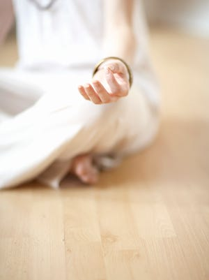 Woman sitting in sukhasana position, focus on hand