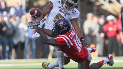 Ole Miss' Vince Sanders, right, battles with Mississippi State's Jamerson Love for a pass in Saturday's game in Oxford.