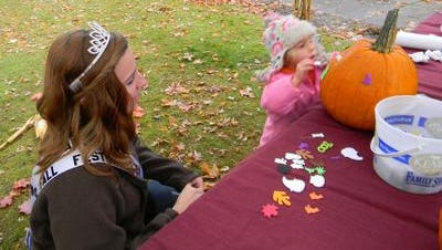 2012 Granton Fall Festival queen Olivia Verkilen helps Eleanore Jacobs, 4, put stickers on her pumpkin at Tufts' Mansion in 2012.