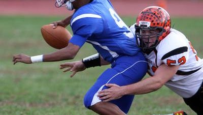 Naquese Johnson, #9, is sacked during a 2013 football game in Lakewood.