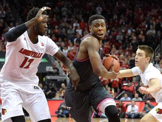 Virginia Tech's Justin Bibbs (10) fights his way through the defense of Louisville's Mangok Mathiang (12) and Ryan McMahon (30) during the first half of an NCAA college basketball game, Saturday, Feb. 18, 2017, in Louisville, Ky. (AP Photo/Timothy D. Easley)