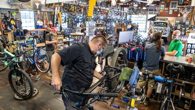 """Bike Surgeon's Mike """"Big Mike"""" Eschmann works on a customer's bike in the service area in O'Fallon, Ill. The Bike Surgeon has been busy since COVID-19 hit the region."""