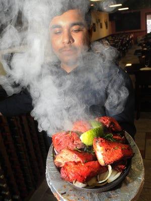 Manager Nick Raheja, of The Masala Twist, displays the Chicken Tandoori Sizzler.