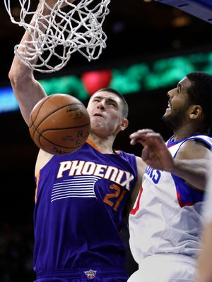 Phoenix Suns center Alex Len (21) dunks the ball as Philadelphia 76ers forward Brandon Davies follows in the first half on an NBA basketball game, Friday, Nov. 21, 2014, in Philadelphia.