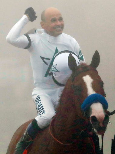 Justify with Mike Smith atop celebrates after winning