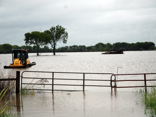 A farm vehicle became an island in a flooded field