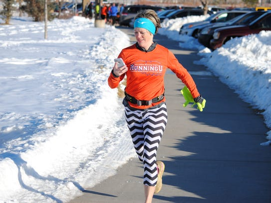 Kirsten Schuster checks her phone while running a race
