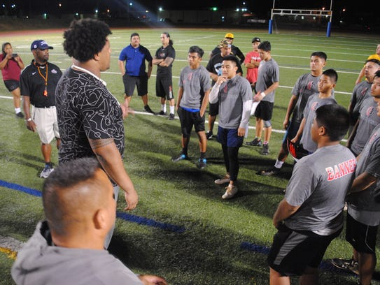 Cleveland Browns offensive tackle Zach Banner address players at the end of the football camp held Jan. 30, 2018, at the Guam High School football field.