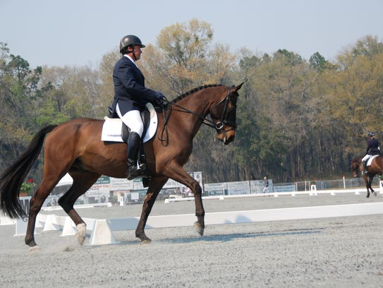 David O'Connor rides outside the dressage ring preparing