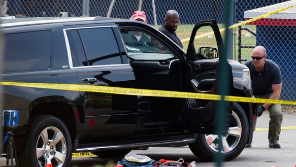 FBI inspectors examine a SUV at the scene of a June
