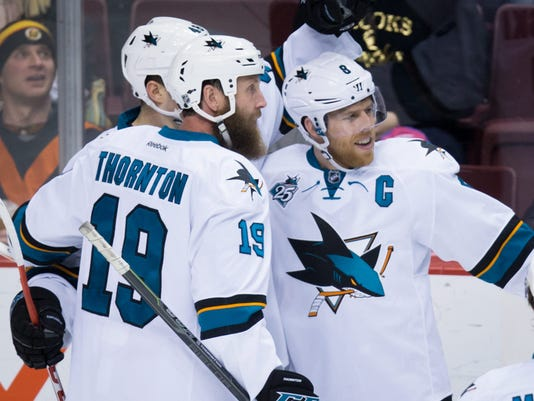 San Jose Sharks' Joe Pavelski, right, Joe Thornton, front left, and Tomas Hertl, of the Czech Republic, celebrate Pavelski's goal against the Vancouver Canucks during the second period of an NHL hockey game Tuesday, March 29, 2016, in Vancouver, British Columbia. (Darryl Dyck/The Canadian Press via AP)