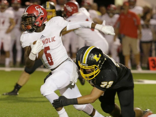 Catholic New Iberia running back Jaden Stokes is tripped up by Loreauville's Chase Clifton during the first quarter of Catholic's game with Loreauville on Friday night October 7, 2016 in Loreauville.JOHN ROWLAND / FOR THE ADVERTISER