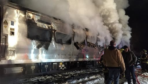 A Metro-North Railroad passenger train smolders after hitting a vehicle in Valhalla, N.Y., on Tuesday, Feb. 3, 2015.