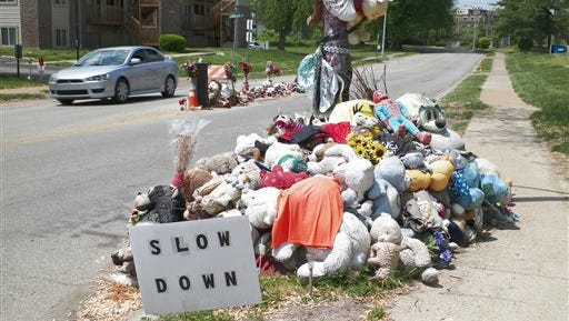 A car passes two makeshift memorials to Michael Brown Tuesday, May 5, 2015, near where the unarmed, black 18-year-old was shot and killed last August by white Ferguson, Missouri, Police Officer Darren Wilson. The 9-month-old shrine in the middle of the road, marking the spot were Brown fell dead, has been hallowed symbol of a new civil rights movement over race and policing _ and to others, now more of an eyesore and a road hazard. The city, Brown's family and a Washington-based mediator are grappling with the thorny question of whether to remove or replace it and risk further inflaming racial tensions.